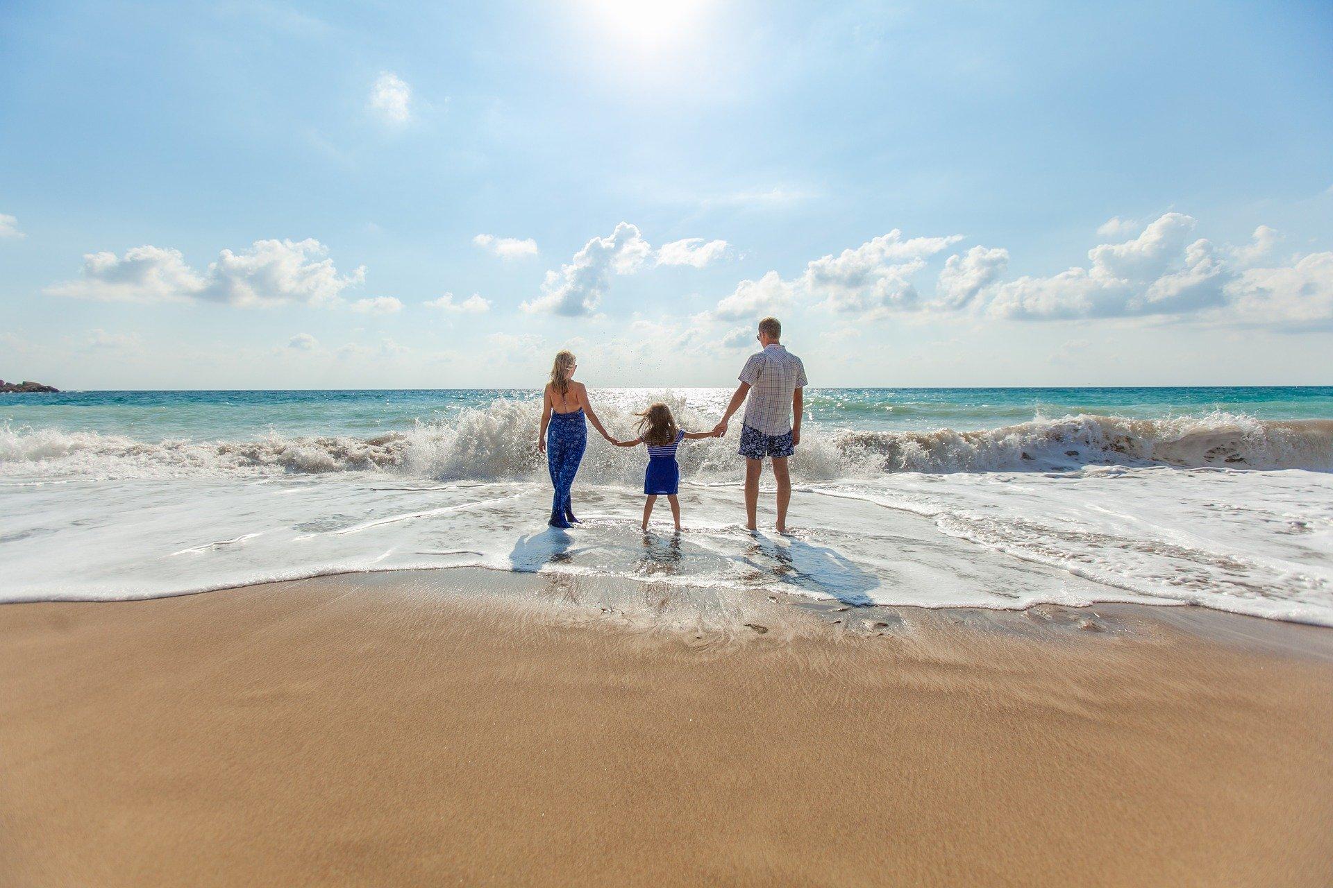 mãe pai e filha de mãos dadas na beira do mar