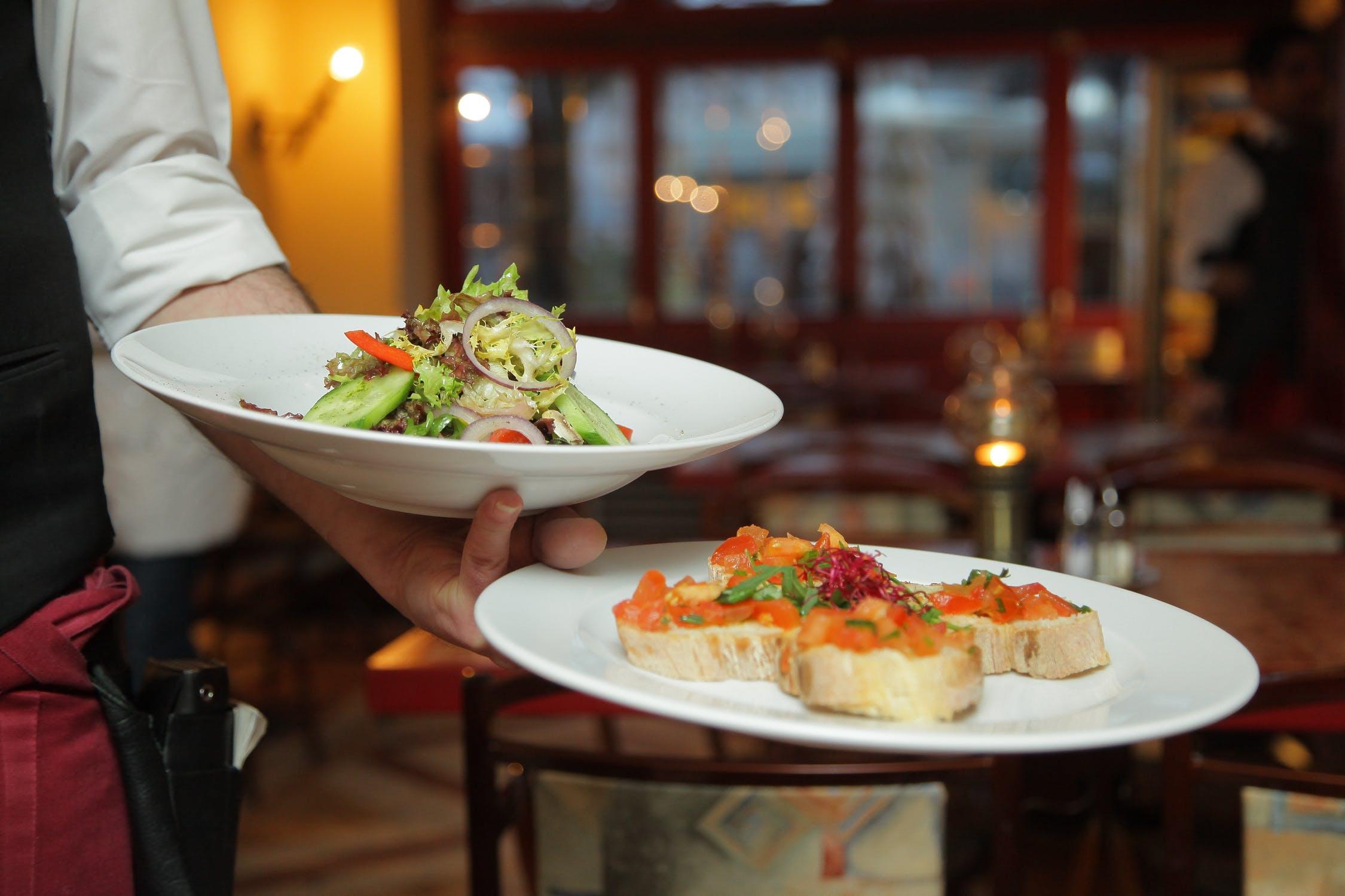 Homem servindo dois pratos para manter a alimentação equilibrada