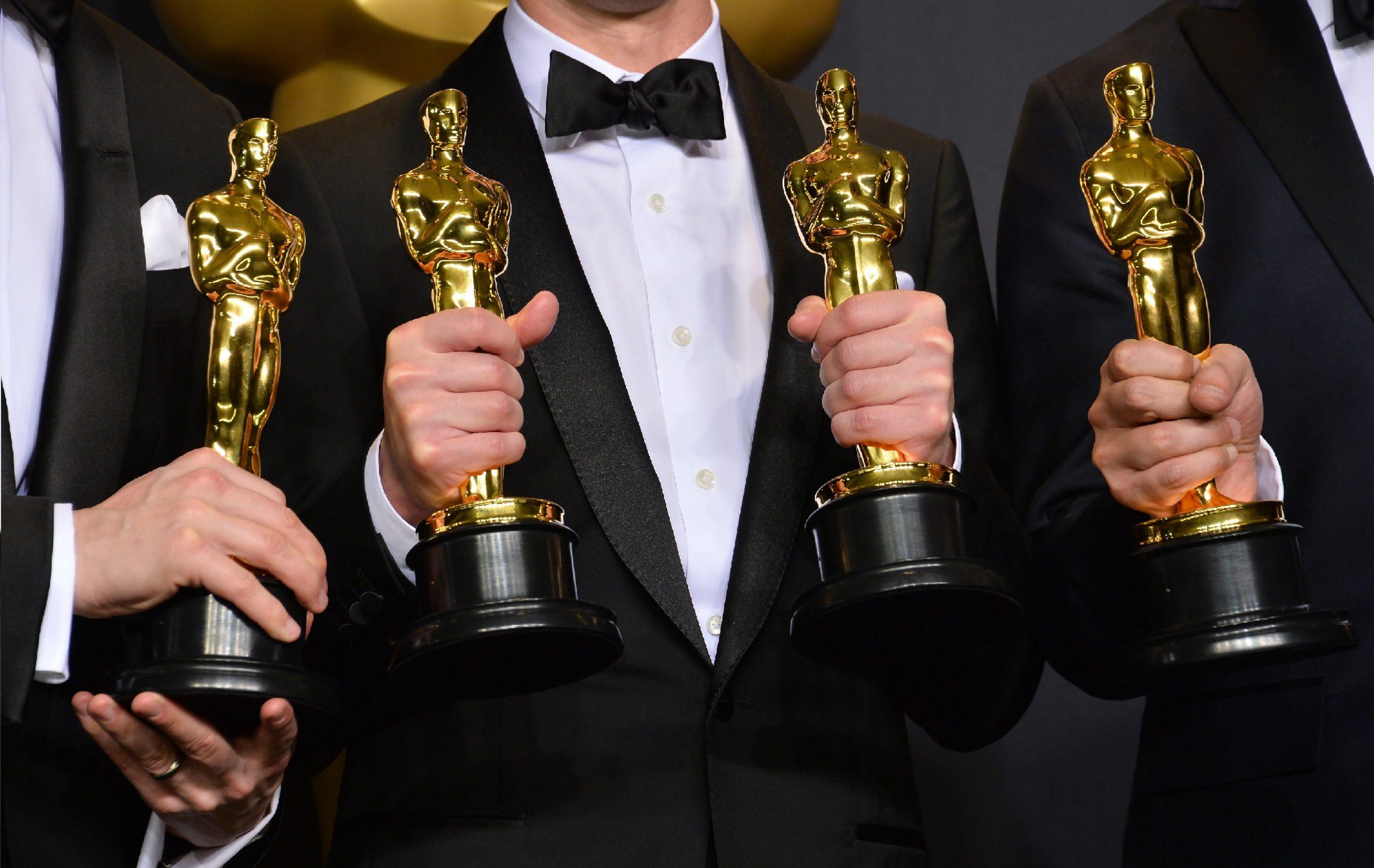 Pessoas de terno segurando troféu de óscar de indicações de filmes