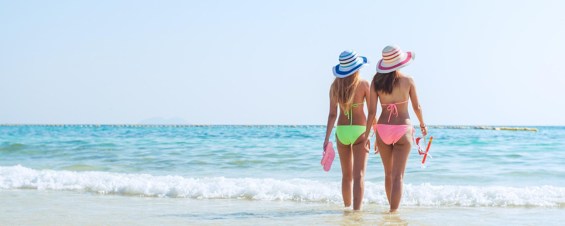 duas mulheres na praia usando diferentes tipos de biquínis